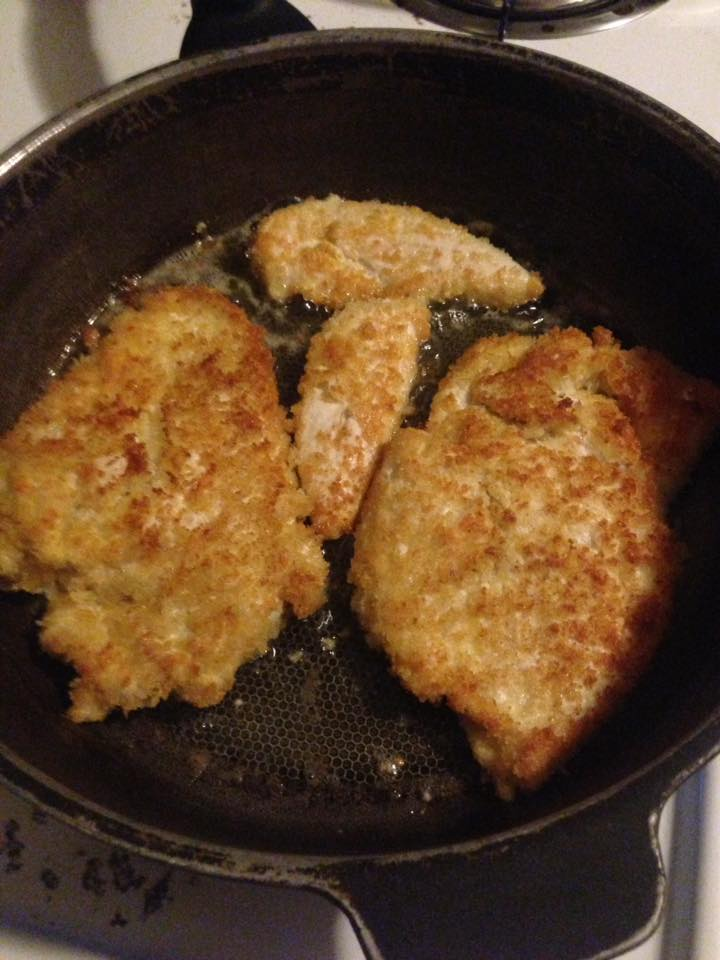 breaded chicken breast in frying pan after being flipped